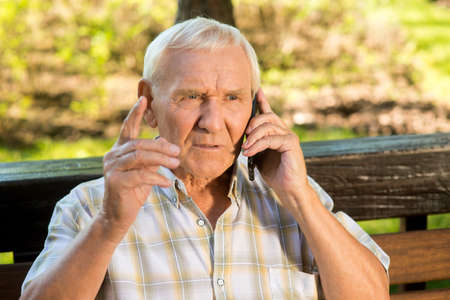 Senior man with mobile phone. Old guy with serious face. Listen to me, son. Giving a wise advice. Stock Photo