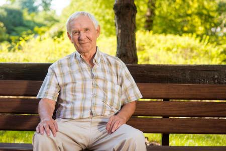 viejo hombre se sienta en el banco. hombre de edad avanzada está sonriendo. Se merece un buen descanso. Todos los problemas quedan atrás.