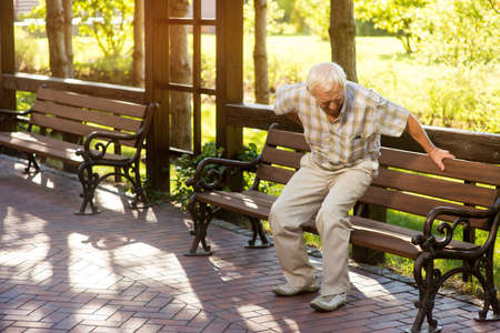 Senior man holding his back. Old male near park bench. Strong pains in spine. Need of medication and therapy. Stock Photo