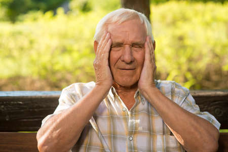 impacts: Elderly man has headache. Old guy holds his head. High blood pressure and temperature. How stress impacts health.