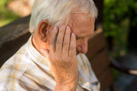 stressful: Senior man holds his head. Old person has headache. Pain is getting stronger. What a stressful day. Stock Photo