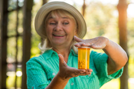 new medicine: Woman with pill bottle smiling. Lady holding medicine. New vitamin formula. Drug that strengthens immunity.