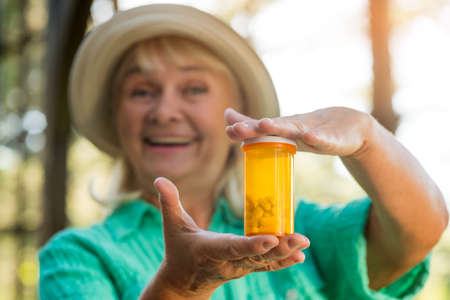 new medicine: Smiling woman with pill bottle. Lady holding medicine container. New type of antidepressant. Use the smallest dose.