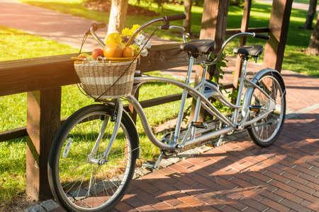 Tandem fiets in het park. Rieten mand met fruit. Breng weekend in de open lucht. Geniet van rust en op te slaan gezondheid. Stockfoto