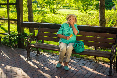 recover: Mature woman eating pills. Lady sitting on park bench. Medicine prescribed by the doctor. Quickly recover from illness.