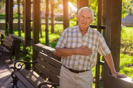 Elderly man has heart ache. Senior male near wooden fence. Every movement increases pain. Health was damaged long ago.