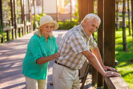 Senior male leans on fence. Elderly couple outdoors. Pains in lower back. Old traumas influence health. Фото со стока