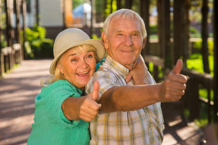 get tired: Elderly woman hugging man. Senior couple showing thumbs up. Loving hearts dont get tired. Many years spent together.