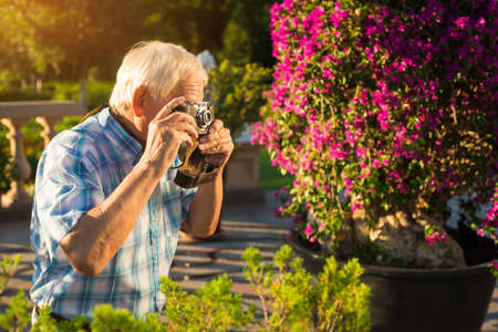 more mature: Senior man holding camera. Elderly male outdoors. Make few more pictures. Nature inspired photographer.
