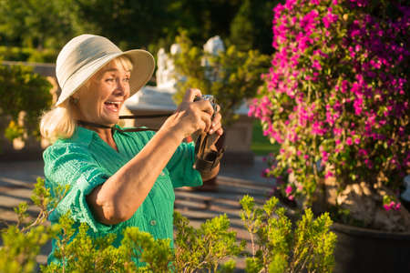 find us: Senior woman holding camera. Lady in hat is laughing. Find yourself a new hobby. Amazing life around us.