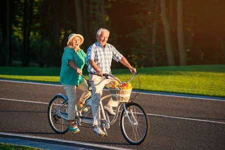 タンデム自転車に乗る年配のカップル。人々 は道に乗る。ペダルの回転が加速。時間とのレース。