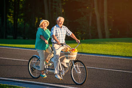 Senior couple riding tandem bike. People ride on the road. Spin the pedals faster. Race with the time.