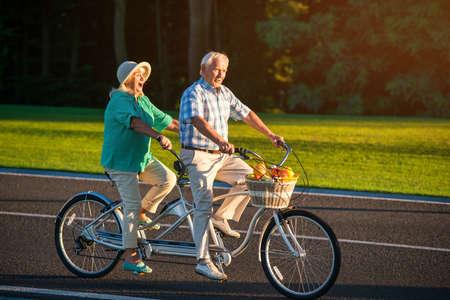 Senior paar op fiets achter elkaar. Fiets met fruitmand. Liefhebbers van snelle rit. Racers op de hoofdweg. Stockfoto
