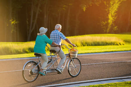 Senior couple on tandem bicycle. Bike on the road. Faster than wind. The racer inside me. Foto de archivo