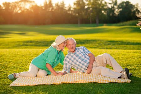warmest: Senior couple lying on blanket. Two people on meadow. The warmest feelings. Our place under the sun.