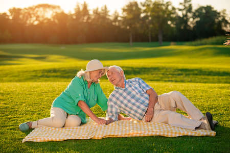 bigger: Elderly couple lying on blanket. Smiling senior man and woman. Drowning in your eyes. Didnt dream of bigger happiness.