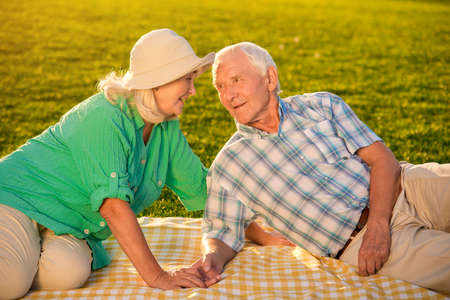 warmth: Senior people on meadow. Couple looking at each other. Im always with you. Warmth of our hearts.