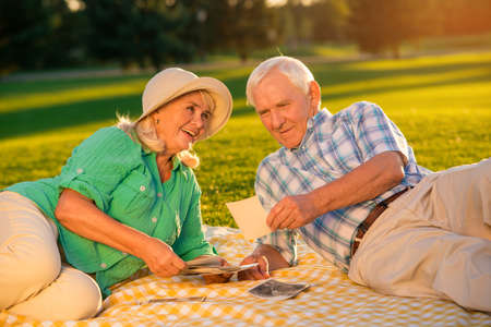 Couple lying on meadow. Senior man looking at photographs. That was long time ago. I remember our first date. Stock Photo