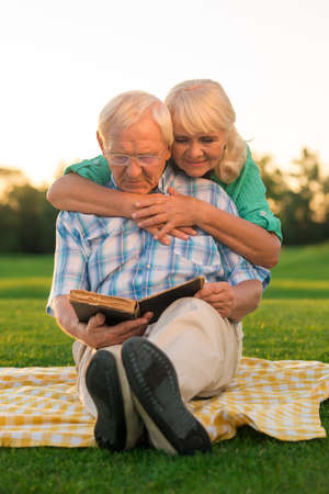 favorite book: Senior couple reads book. Two people sitting on meadow. Our favorite story. Turn the page.