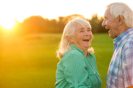 jokes: Senior couple laughing. Man and woman outdoors. Sense of humour. Old funny jokes. Stock Photo