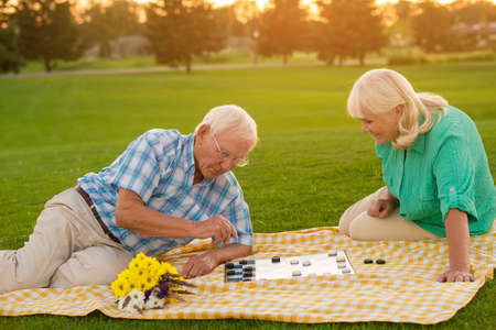 weaknesses: Senior couple playing checkers. Blanket on the meadow. Smart move, darling. I know your weaknesses.