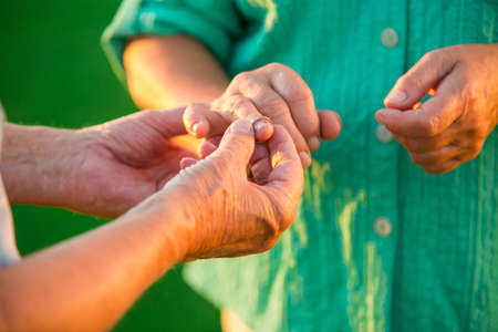 Man puts ring on woman. Hands of senior couple. Its never too late. Open your heart to love. Stock Photo