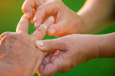 Woman puts ring on man. Hands of old couple. I wont ever leave you. Love is mutual.