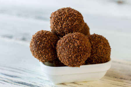 freshly cooked: Brown sweets in a bowl. Small desserts covered in crumbs. Freshly cooked chocolate rum balls. Sweet dish with alcohol.