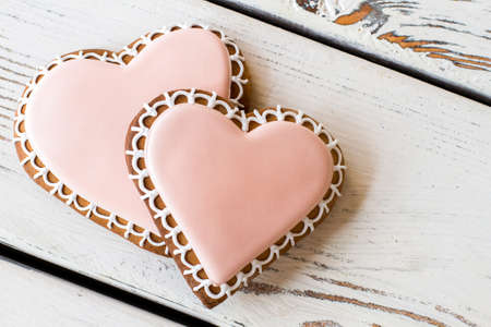 Two heart-shaped biscuits. Cookies with light pink frosting. Treats for those in love. Recipe of happy life.