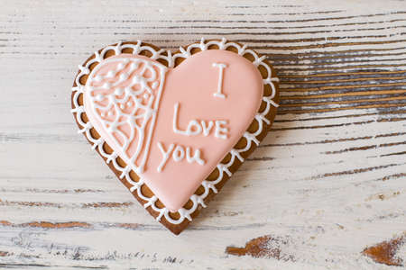 Heart biscuit with inscription. Light pink frosted cookie. Little present sent with love. Pink glaze and white chocolate. Banco de Imagens