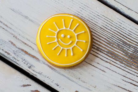 Yellow sun biscuit. Top view of iced cookie. Tasty homemade pastry with glaze. World will smile to you. Stock Photo