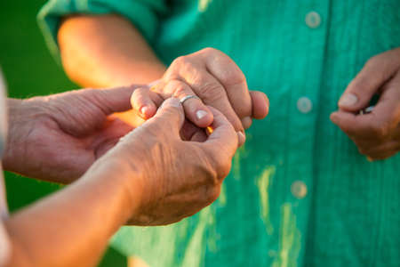 no fear: Man putting ring on lady. Hands of a senior couple. Fill your heart with love. Have no fear.