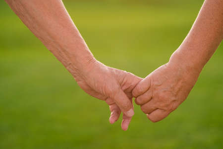 let go: Couples hands on green background. Hands of two seniors. Not a step without you. Dont let go.