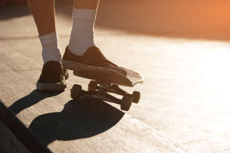 no fear: Skateboard and feet. Legs in slip-ons. Have no fear of failures. Skills come with time. Stock Photo