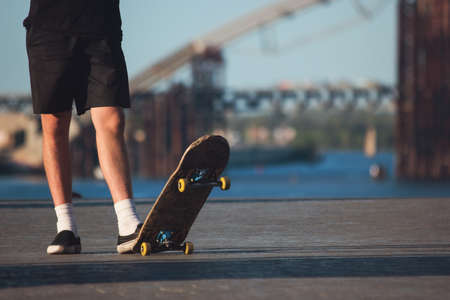 those: Guy with skateboard outdoor. Legs of skateboarder standing. Sport of young and fearless. For those who love risk.