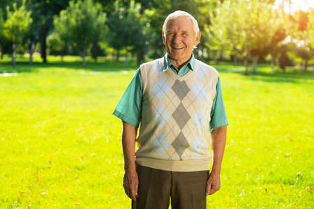 remembered: Old guy smiling outdoor. Man on park background. I remembered a funny story. Life is changing so fast. Stock Photo
