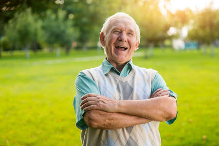 witty: Senior man is laughing. Male with crossed arms outdoor. What a witty joke. You raised my mood. Stock Photo