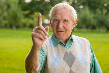taught man: Man with raised finger. Old male looking at camera. Remember what Ive taught you. Important lesson in life.