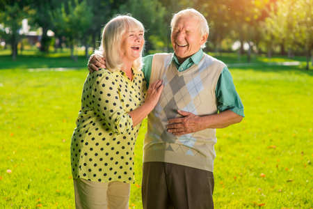 Couple of seniors laughing. Old people outdoors. Not a day without laughter. Look at everything with humor. 版權商用圖片