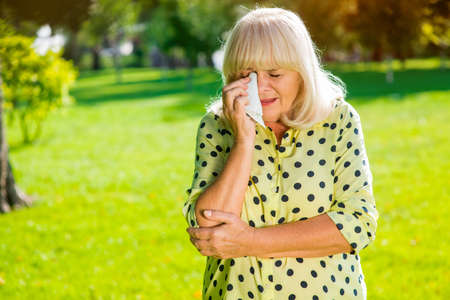 difficult period: Lady wiping eye with handkerchief. Sad senior woman. I lost everything I had. Difficult period of life.