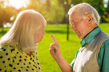 Man points finger at woman. Old grumpy couple. Difficulties in relationships. You dont understand me.
