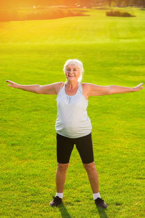 staying fit: Senior woman doing exercise. Smiling female outdoors. Stay healthy and energetic. Fitness in the open air.