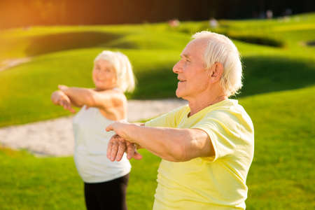 Senior man does exercise. Elderly guy outdoors. How to strengthen the organism. Way to health. Stock Photo
