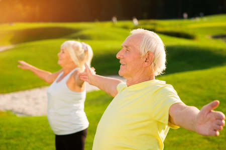 staying fit: Senior man with outstretched arms. Smiling male outdoor. Stay healthy and strong. Gymnastics in summertime. Stock Photo