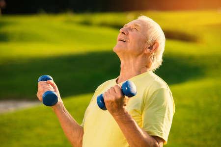 Senior man met dumbbells. Persoon lacht en kijkt omhoog. Kracht en concentratie. Gemotiveerd door het doel.