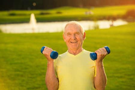 Senior man met halters lacht. Oude man op de natuur achtergrond. Lift gewichten om sterker te worden. Sport is mijn leven. Stockfoto