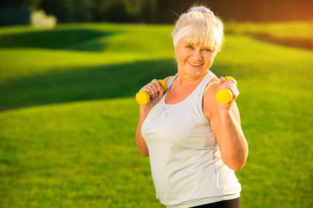 Elderly woman with dumbbells. Lady in tank top outdoor. Healthy muscles and joints. Sport as part of life. Stock fotó
