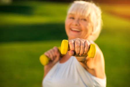 Senior vrouw met halter. Bejaarde dame met lachende gezicht. Ik train om gezonder te worden. Vecht met de luiheid.