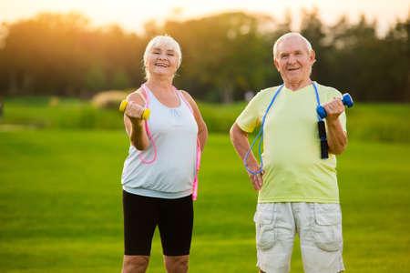 Un couple âgé avec des haltères. Les gens font de l'exercice et sourient. Les sportifs ne vieillissent jamais. L'humeur et la motivation. Banque d'images