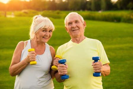 Couple with dumbbells is smiling. Old man and woman outdoors. All goals are achievable. Stay healthy and motivated.